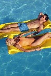 Couple reclining on rafts floating in pool